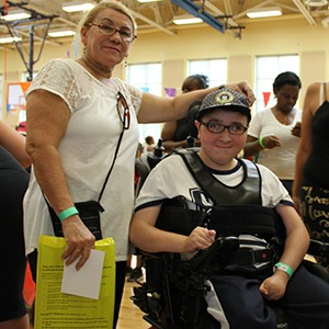 Teenager in a wheelchair with his caregiver at an ECC event