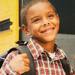 Young boy happy to get on school bush holding backpack strap